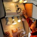 A child learning about light bulbs and their difference in wattage.